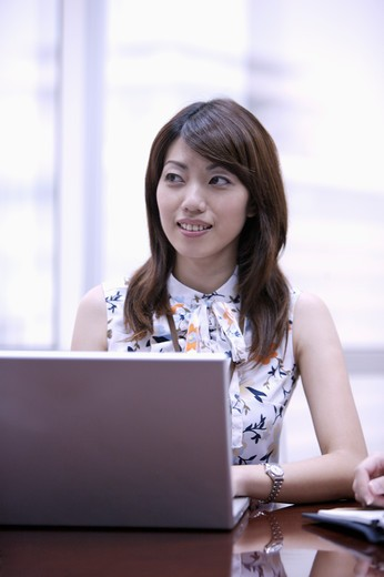 Stock Photo: 1397R-69123 Young woman using laptop and looking away