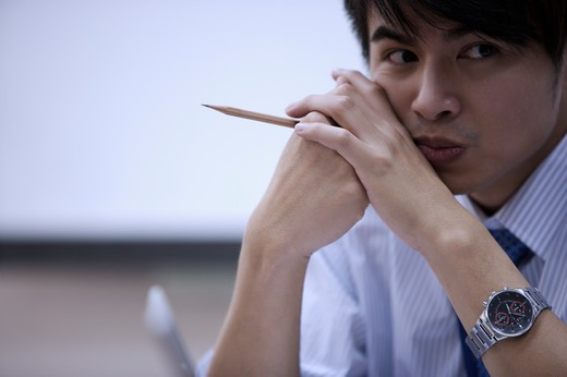 Stock Photo: 1397R-69128 Young man holding a pencil and looking away