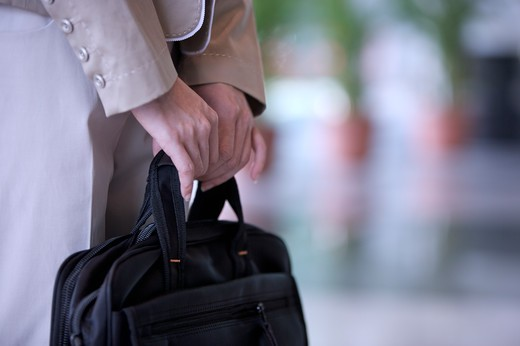 Stock Photo: 1397R-69131 Close-up young woman's hands holding a briefcase