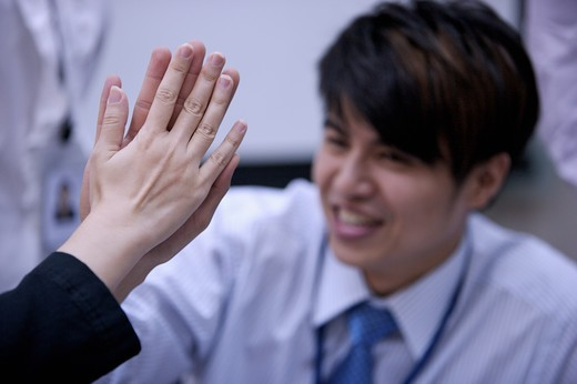 Young man smiling and doing give me five : Stock Photo