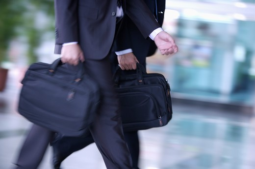 Stock Photo: 1397R-69142 Two businessmen walking and holding briefcase together