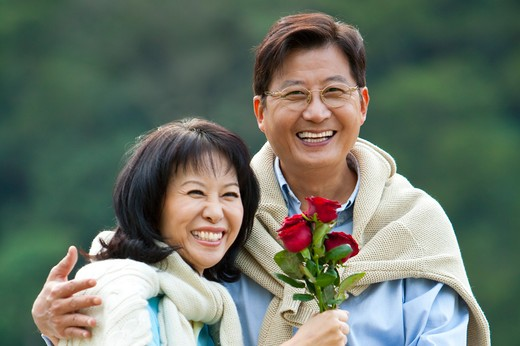 Couple, Couple bonding together, holding red roses and smiling happily : Stock Photo