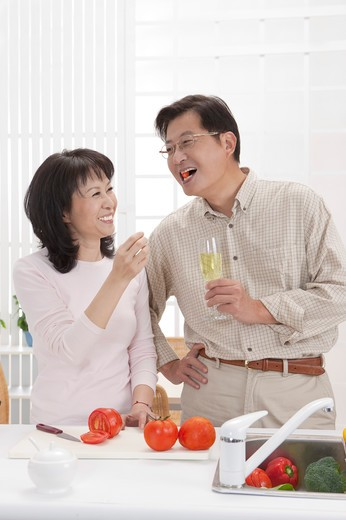 Stock Photo: 1397R-69232 Couple, Couple eating food in kitchen and smiling happily