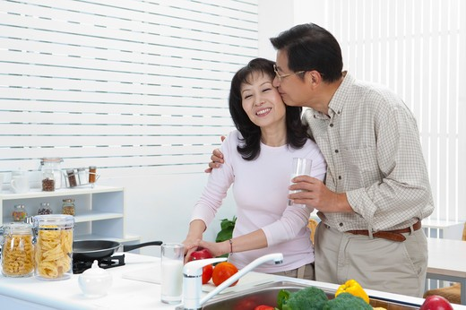 Stock Photo: 1397R-69252 Couple, Husband kissing wife in the kitchen and holding a glass of milk