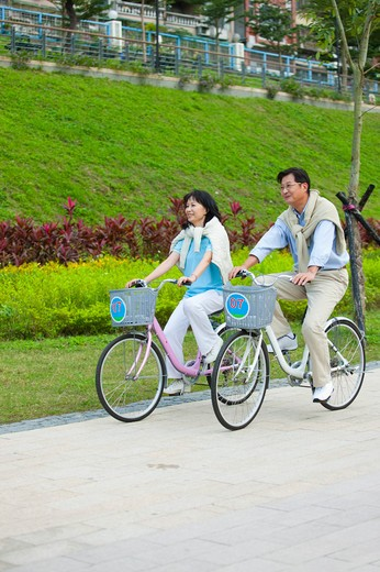 Stock Photo: 1397R-69256 Couple, Couple riding on bikes together