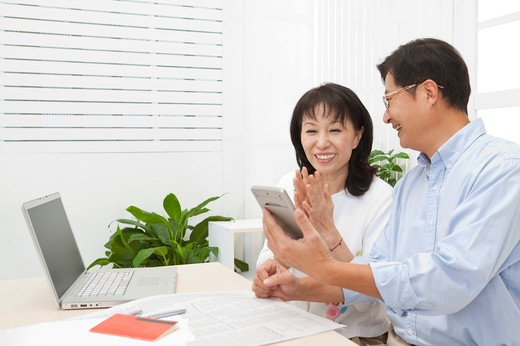 Couple, Couple looking at the calculator with smile : Stock Photo
