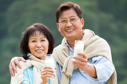 Stock Photo: 1397R-69268 Couple, Couple holding a glass of drink and smiling at the camera