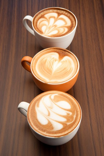 Stock Photo: 1397R-69298 Coffee, Close-up of three cups of cappuccino with pattern on the table