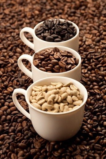 Stock Photo: 1397R-69315 Coffee Bean, Coffee Culture, Close-up of three cups of coffee beans on a stack of coffee beans
