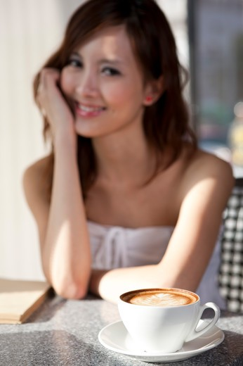 Coffee Break, Young woman sitting with a cup of coffee and looking at the camera with smile : Stock Photo