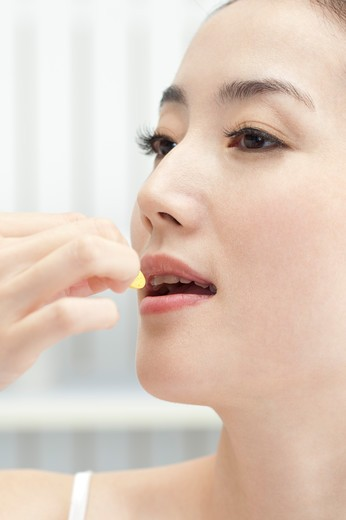 Stock Photo: 1397R-69448 Beauty Treatment, Close-up of woman's face and taking medicine