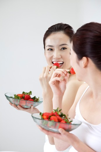Stock Photo: 1397R-69492 Beauty Treatment, Woman looking at the mirror and eating a plate of strawberry