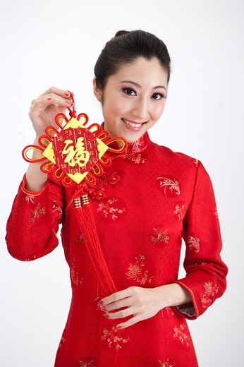 Stock Photo: 1397R-69568 New Year, Young woman wearing Chinese traditional clothing and holding a tassel with smile