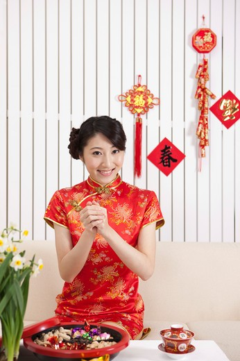 Stock Photo: 1397R-69571 New Year, Young woman wearing Chinese traditional clothing and greeting with smile