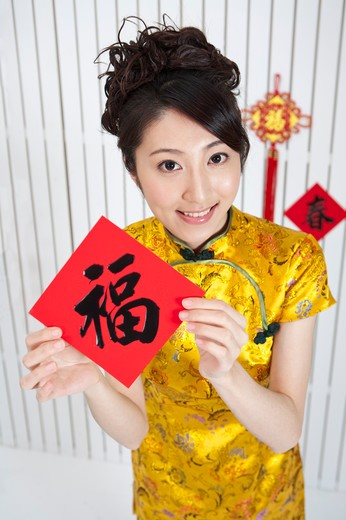 Stock Photo: 1397R-69592 New Year, Young woman wearing Chinese traditional clothing and holding Chinese script with smile