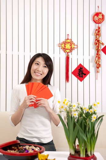 Stock Photo: 1397R-69593 New Year, Young woman holding red envelopes and looking away with smile