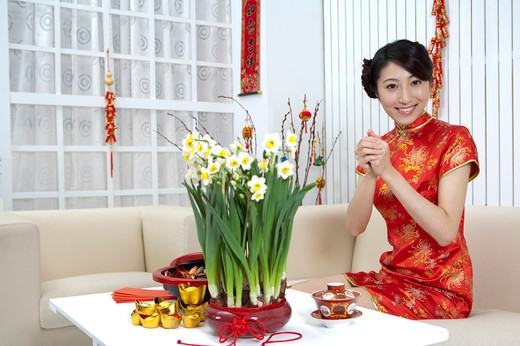 Stock Photo: 1397R-69596 New Year, Young woman wearing Chinese traditional clothing and greeting with smile