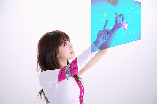 Stock Photo: 1397R-69792 Young woman looking up and touching screen with smile