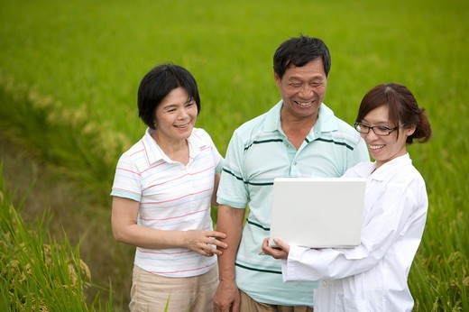 Stock Photo: 1397R-70486 Farmer couple with expert holding laptop in rice field