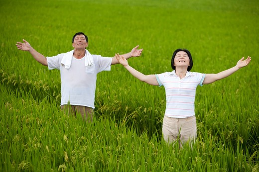 Farmer couple taking deep breath in rice field : Stock Photo
