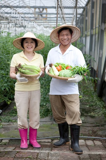 Stock Photo: 1397R-70496 Farmer couple holding vegetables in greenhouse, smiling