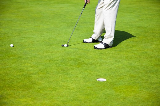 Man putting the golf ball into the hole : Stock Photo