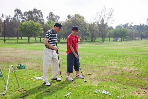 Man teaching teenager boy golf : Stock Photo
