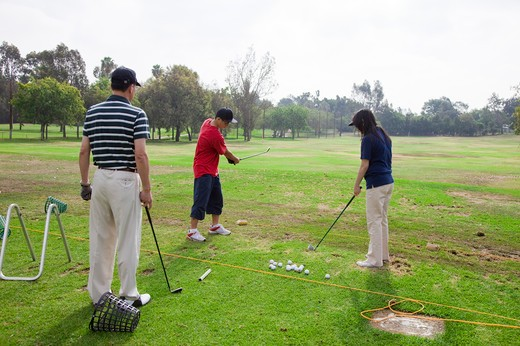 Stock Photo: 1397R-70682 Family practicing golf on the lawn together