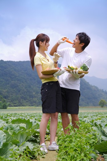 Young couple holding vegetables and smiling happily : Stock Photo