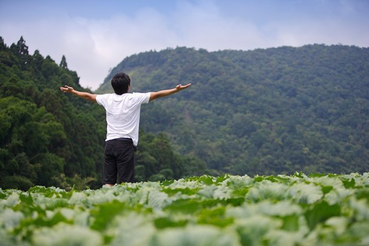 Stock Photo: 1397R-70849 Young man standing in the vegetable garden with arms outstretched