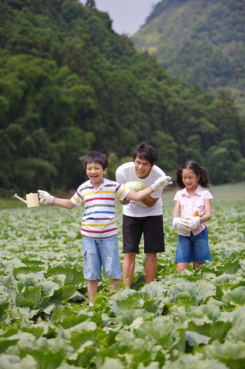 Stock Photo: 1397R-70855 Young man with two children standing in the vegetable garden and smiling