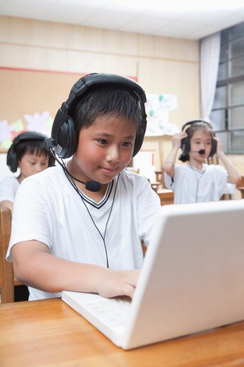 Three children using laptop with headphone together : Stock Photo