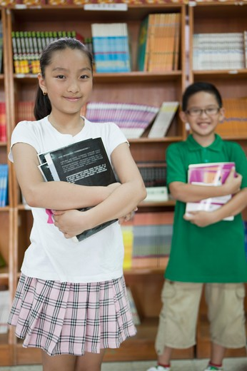 Children holding books and standing in the library : Stock Photo