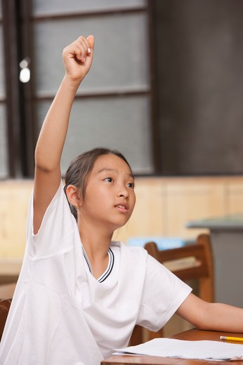 Girl sitting in the classroom with hands raised : Stock Photo