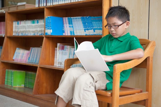 Boy sitting and reading book in the library : Stock Photo