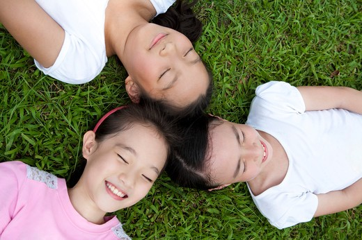 Stock Photo: 1397R-71045 Three girls lying on lawn head to head in a circle