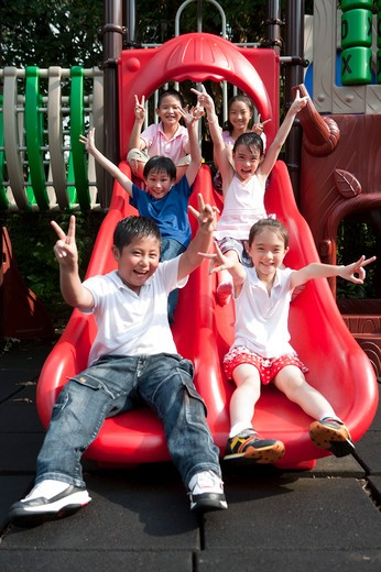 Group of children sitting on slide, giving peace sign : Stock Photo