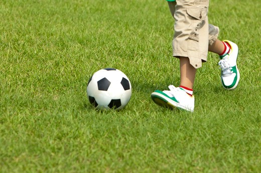 Stock Photo: 1397R-71103 Boy playing football on lawn