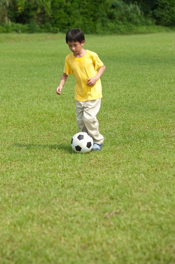 Stock Photo: 1397R-71107 Boy playing football
