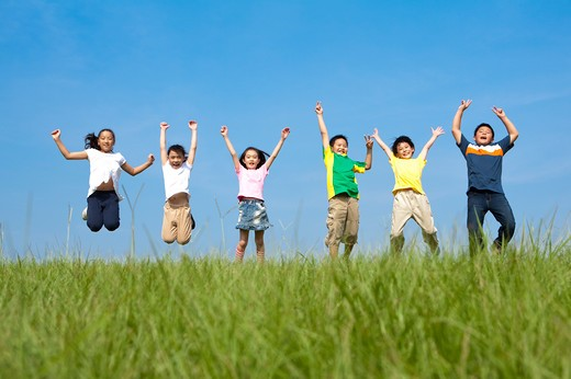 Group of children jumping in mid air on grass : Stock Photo