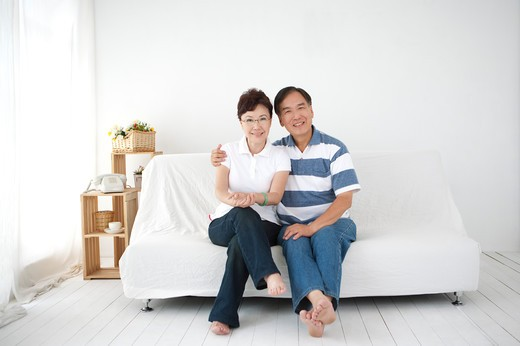 Portrait of a Senior couple sitting in living room : Stock Photo
