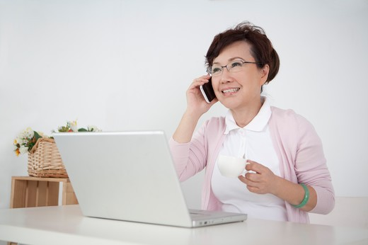 Senior woman sitting in front of a laptop and talking on cell phone : Stock Photo