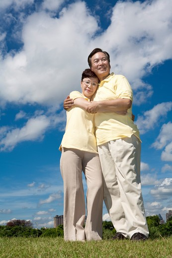 Senior couple standing on lawn and embracing together : Stock Photo