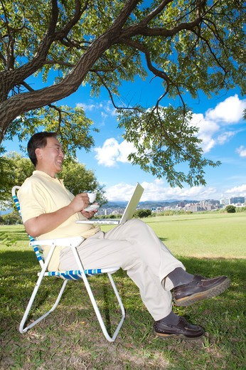 Senior man sitting in deck chair with laptop and coffee in a park : Stock Photo