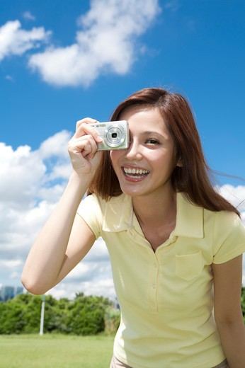 Stock Photo: 1397R-71299 Young woman holding camera and taking picture with smile, Taking Picture