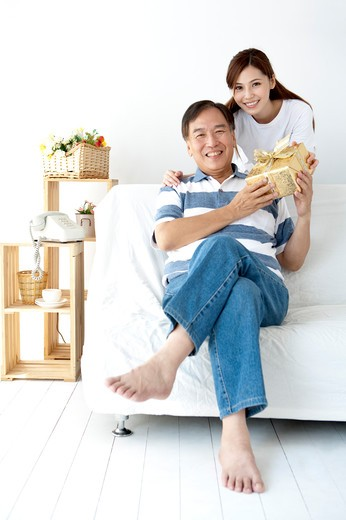Father receiving a gift and smiling happily with daughter : Stock Photo