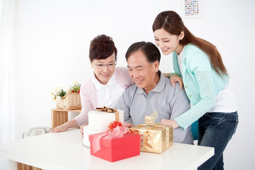 Parents with daughter looking at the gifts and smiling happily together : Stock Photo