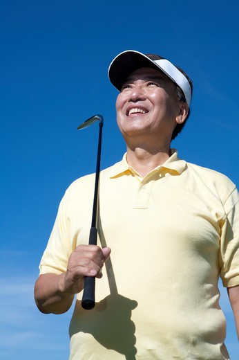Stock Photo: 1397R-71341 Senior man holding golf swing and looking up with smile