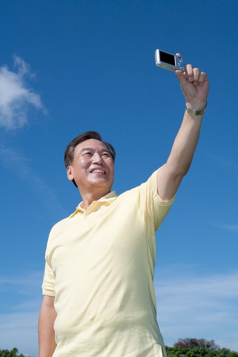 Senior man taking picture and smiling happily : Stock Photo