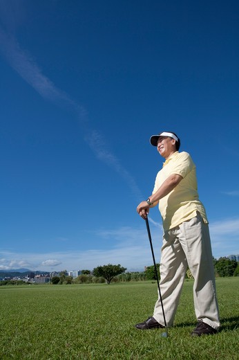 Stock Photo: 1397R-71389 Senior man holding golf swing and standing on the lawn